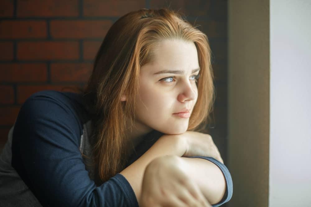 ein Porträt einer traurigen Frau, die aus dem Fenster schaut