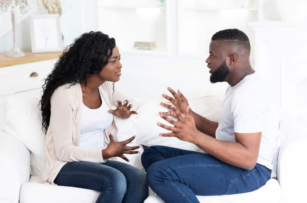 ein afroamerikanisches Paar, das auf der Couch sitzt und streitet