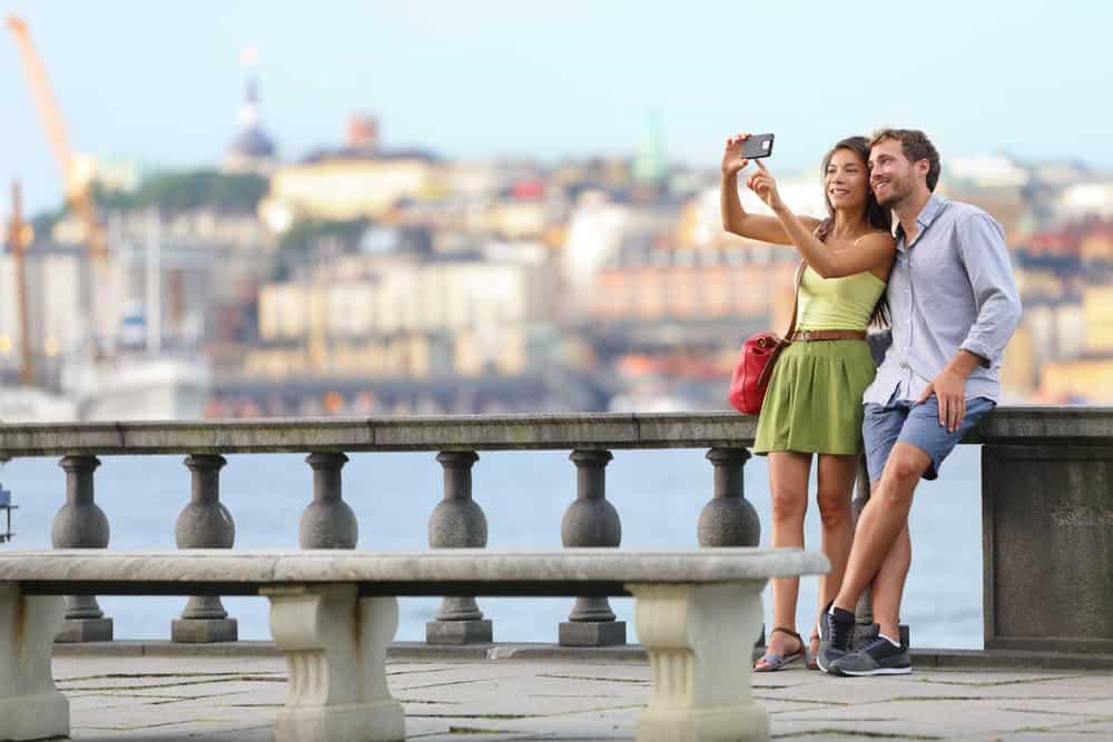 ein liebendes Paar auf einer Brücke, das ein Selfie-Foto macht