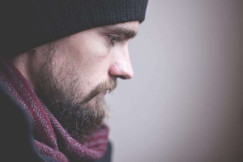 ein nachdenklicher Mann mit einer Mütze und einem Schal um den Hals