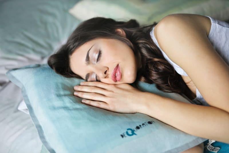 eine Frau, die auf einem weißen Kissen schläft