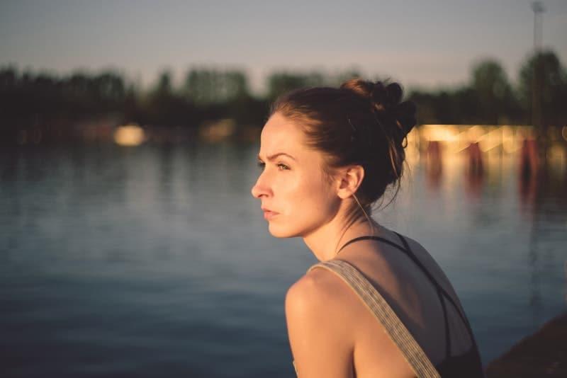 eine depressive Frau, die bei Sonnenuntergang am Wasser steht
