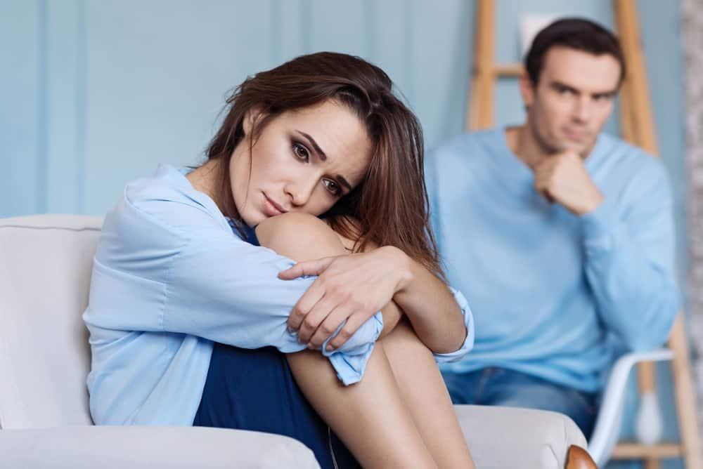 eine zusammengerollte traurige Frau, die in einem Sessel vor einem wütenden Mann sitzt