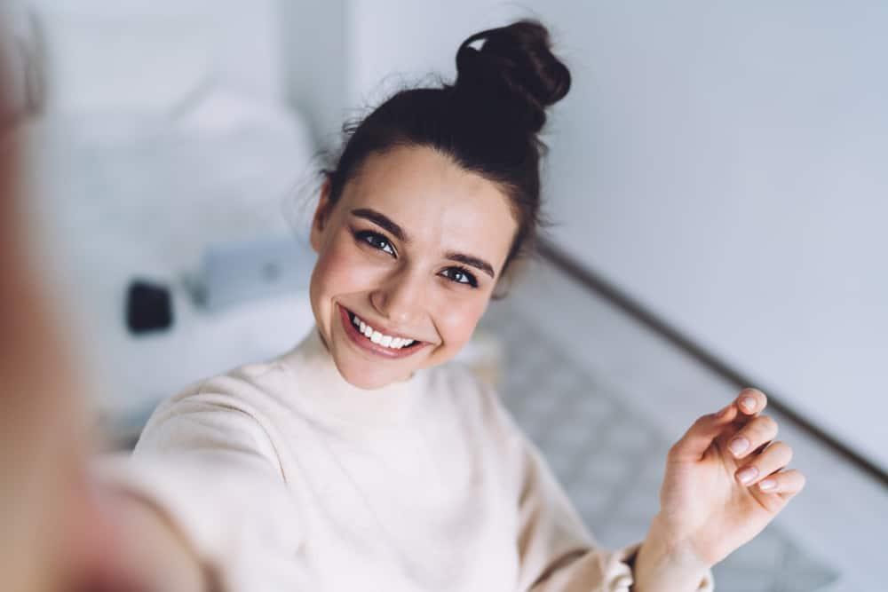 schöne lächelnde Brünette macht ein Selfie-Foto