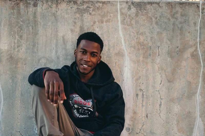 schwarzer Mann sitzt auf der Straße