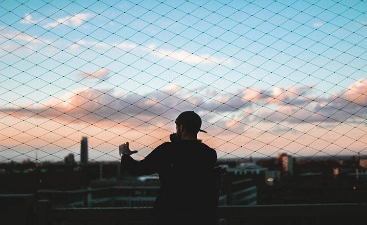 Ein Mann in der Dämmerung steht am Zaun