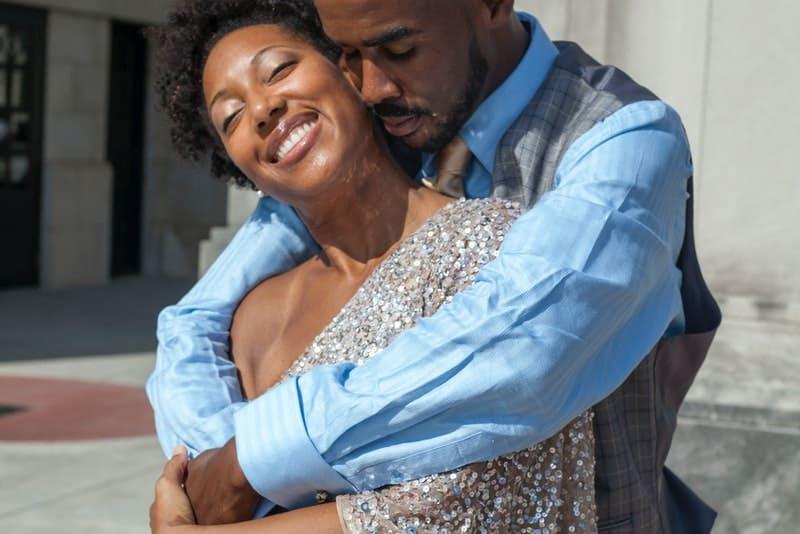 Der schwarze Mann umarmt seine lächelnde Frau von hinten