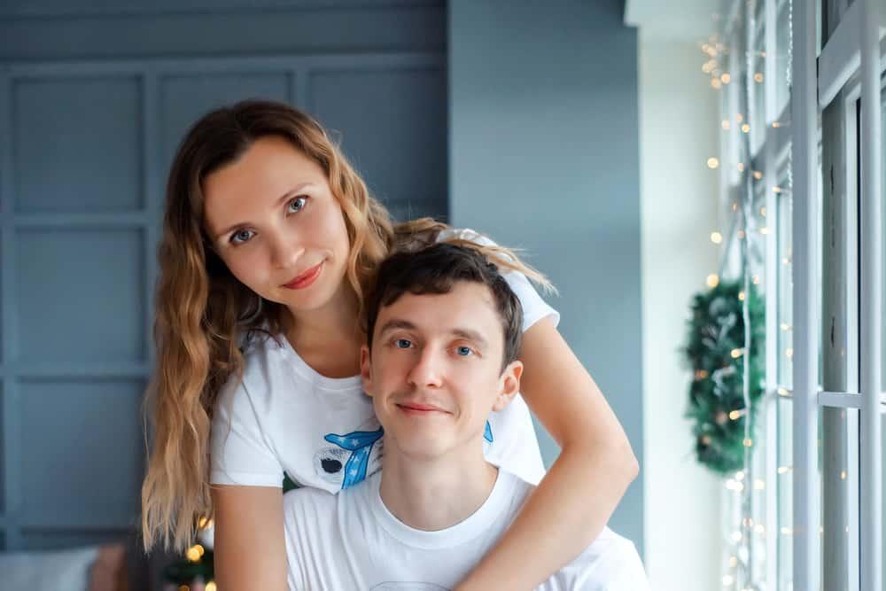 Die Dame umarmt ihren sitzenden Mann