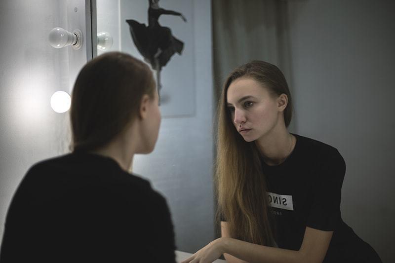 Die Frau steht vor dem Spiegel und schaut sich an