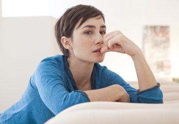 eine kurzhaarige Frau, die nachdenklich auf der Couch sitzt