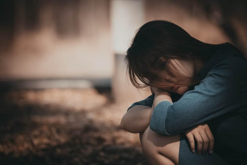 Draußen kauert eine traurige Frau