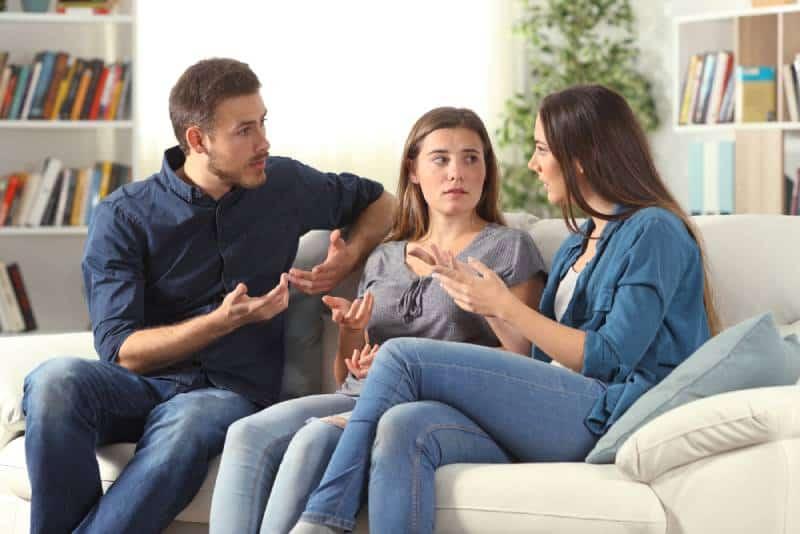 Drei ernsthafte Freunde sprechen auf einer Couch im Wohnzimmer zu Hause sitzend
