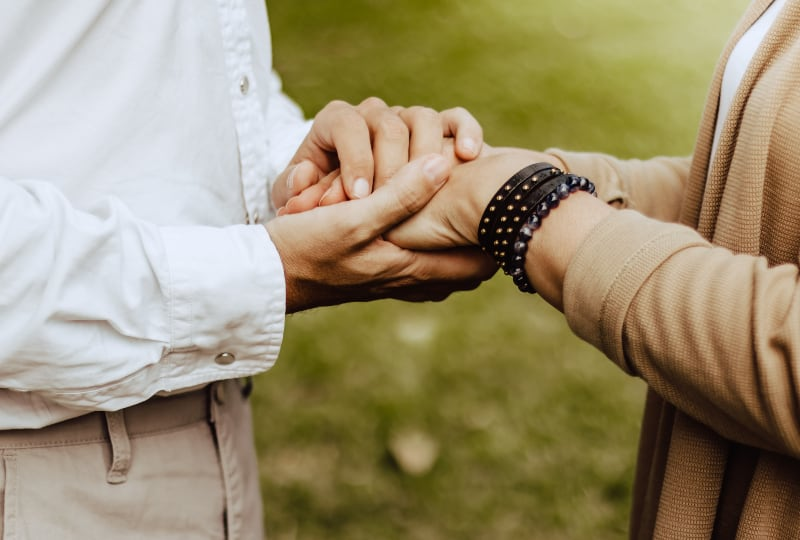 Ein Mann bewacht die Hand seiner Frau