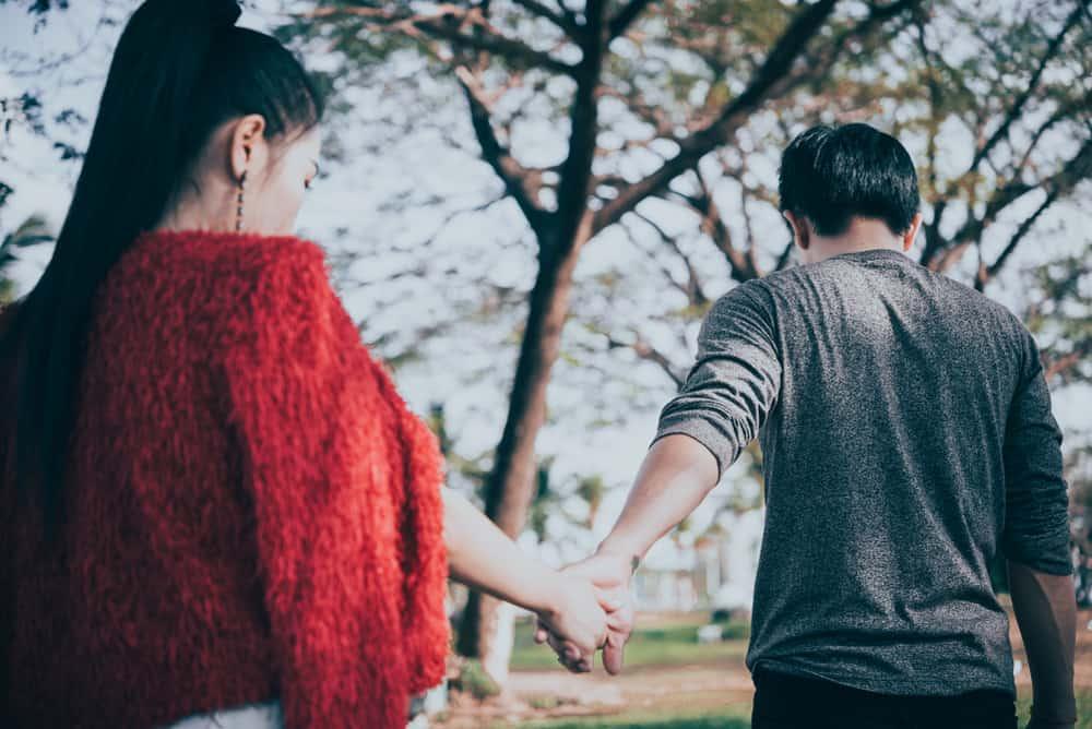 Ein Mann draußen im Park verlässt seine traurige Frau