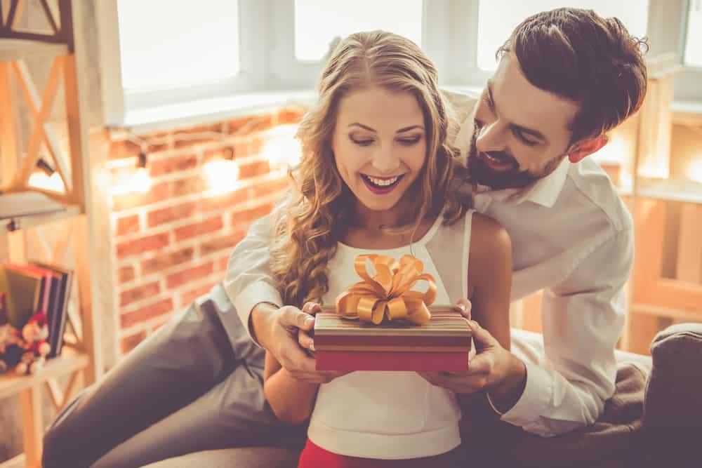 Ein Mann gibt seiner lächelnden Frau ein Geschenk