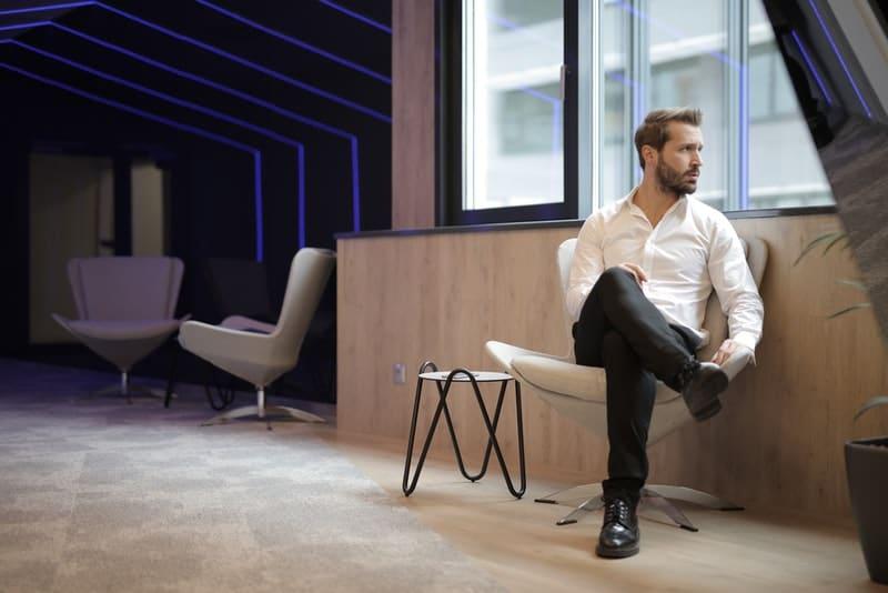 Ein Mann in einem weißen Hemd sitzt und schaut besorgt aus dem Fenster