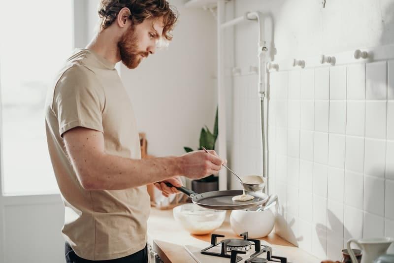 Ein Mann mit Bart bereitet Pfannkuchen zu