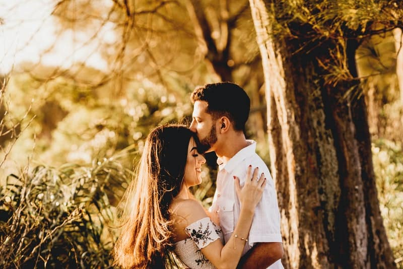 Ein Mann mit Bart küsst die Stirn seiner Frau unter einem Baum