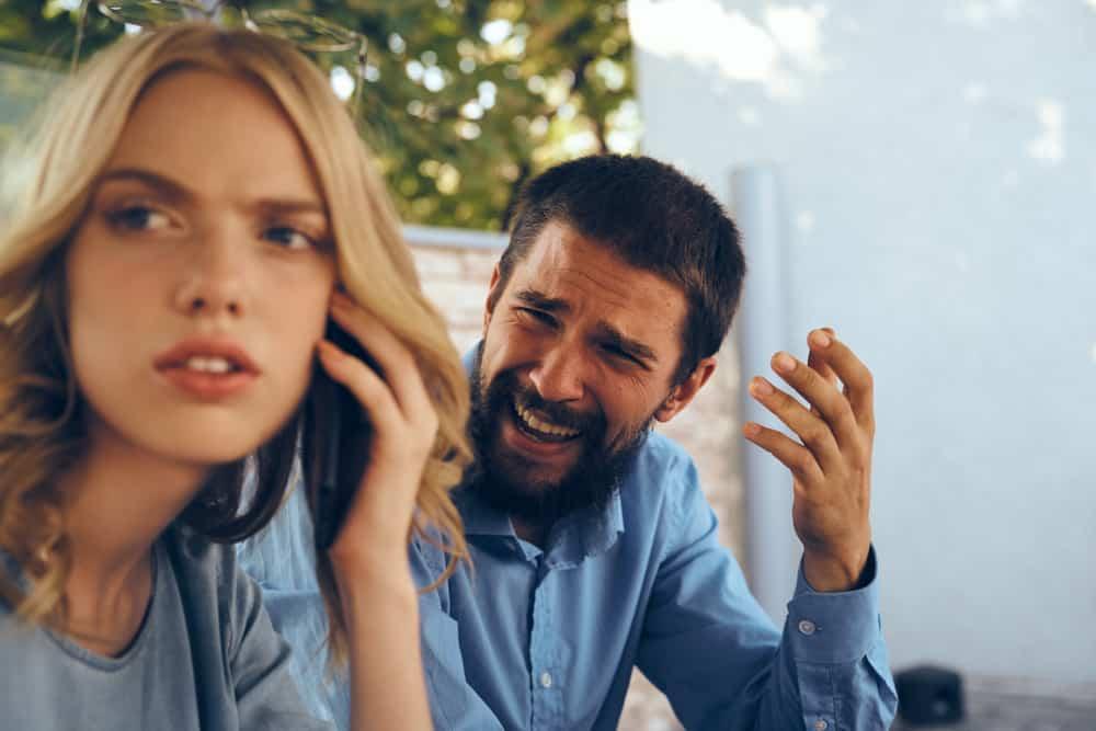 Ein Mann mit Bart kritisiert eine traurige Frau