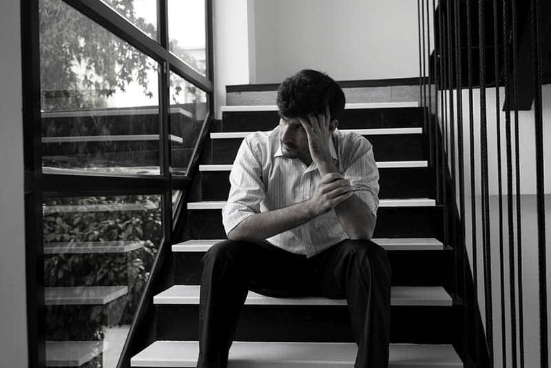 Ein Mann sitzt auf der Treppe und denkt an etwas