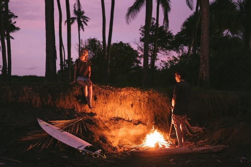 Ein Mann und eine Frau am Lagerfeuer am Strand unter Palmen