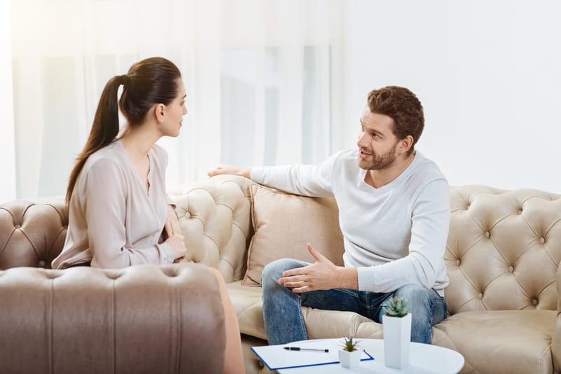Ein Mann und eine Frau sitzen auf einem Baumstamm und reden