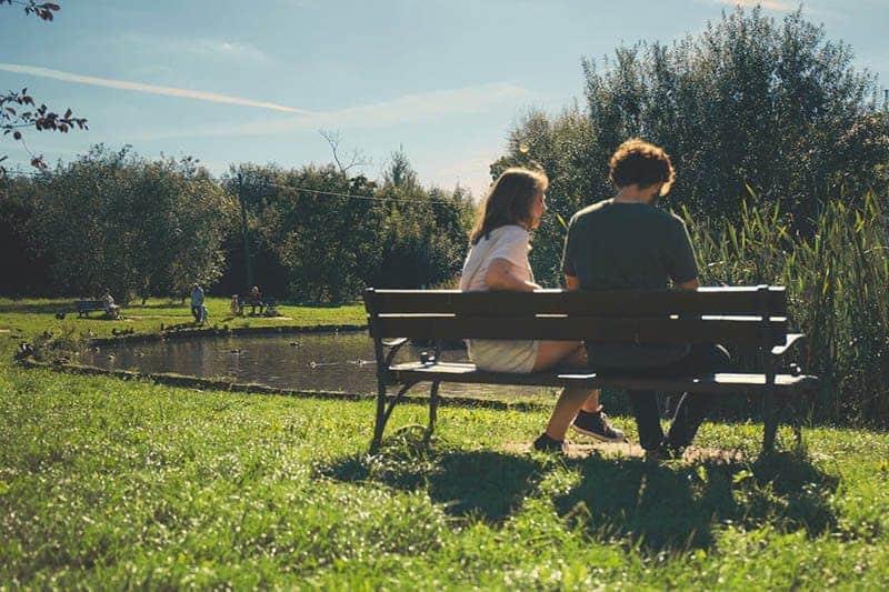 Ein Mann und eine Frau sitzen auf einer Holzbank und unterhalten sich