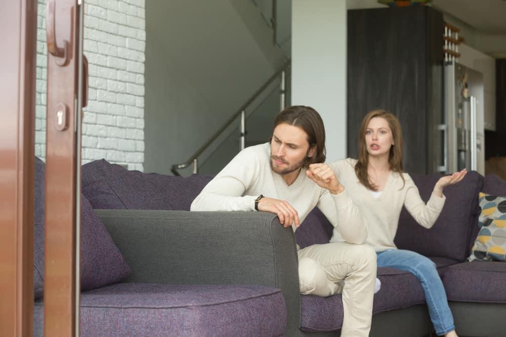 Ein frustrierter wütender Mann sitzt auf der Couch und eine Frau erzählt ihm etwas