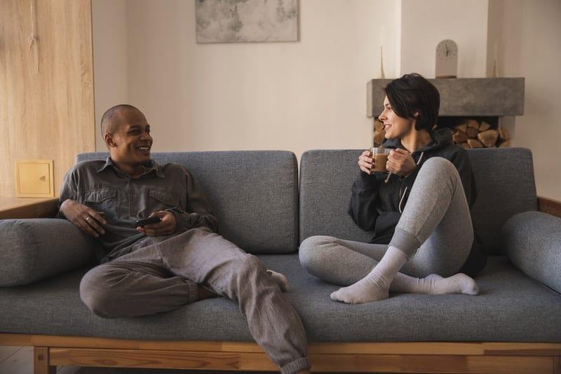 Ein lächelnder Mann und eine lächelnde Frau sitzen auf der Couch und unterhalten sich beim Kaffee