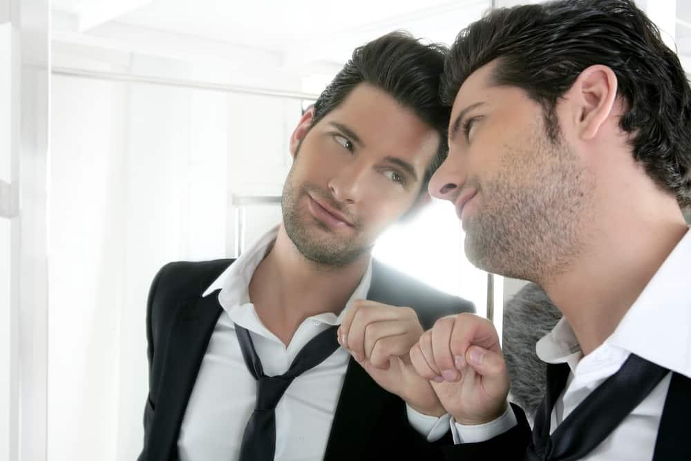 Ein narzisstisch gutaussehender Mann schaut in den Spiegel