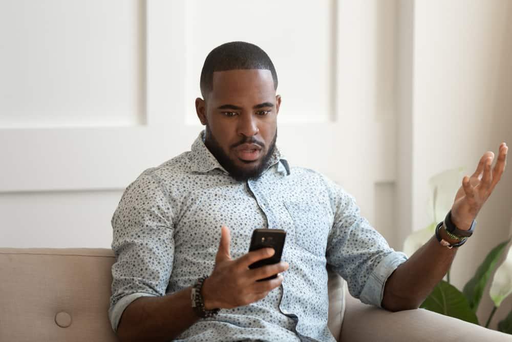 Ein schwarzer Mann in einem Hemd sitzt auf der Couch und schaut verwirrt auf sein Handy