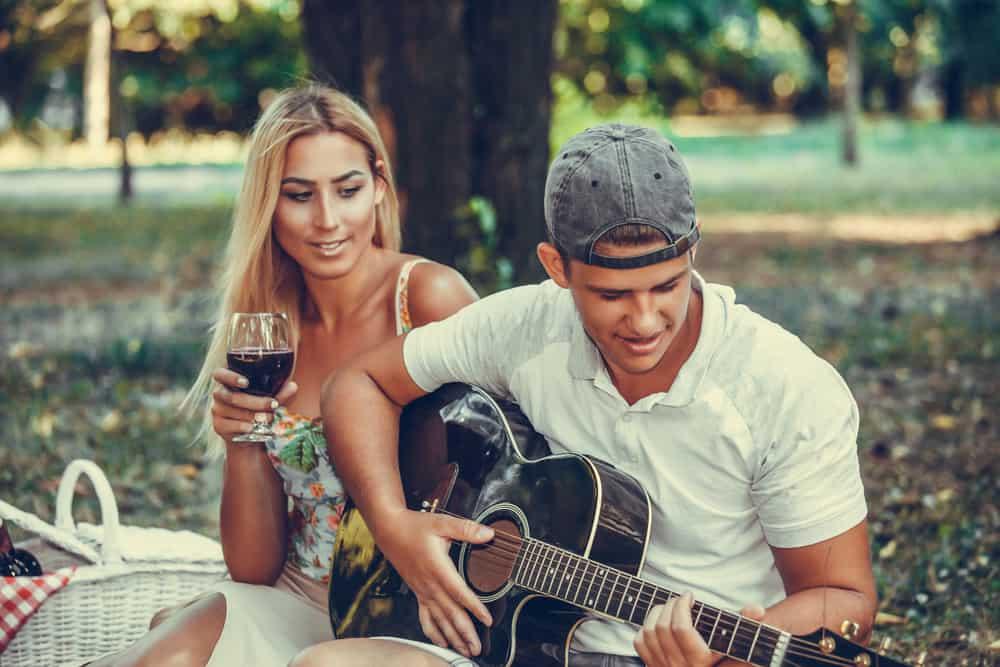 Ein verliebtes Paar genießt ein Picknick mit Gitarre und Wein im Park