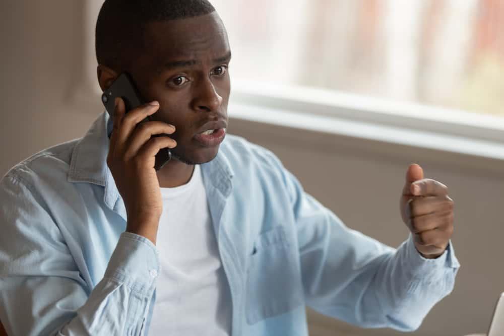 Ein wütender Mann spricht auf seinem Handy und droht mit dem Finger