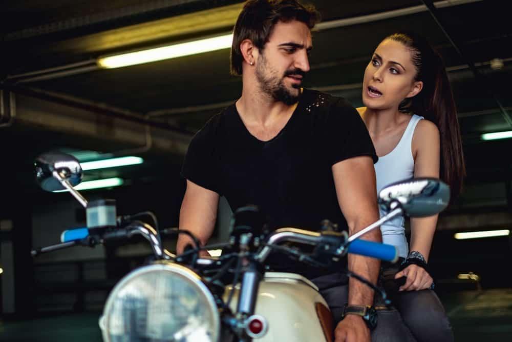 Ein wütendes Mädchen sagt etwas zu ihrem Mann, während er auf einem Motorrad sitzt