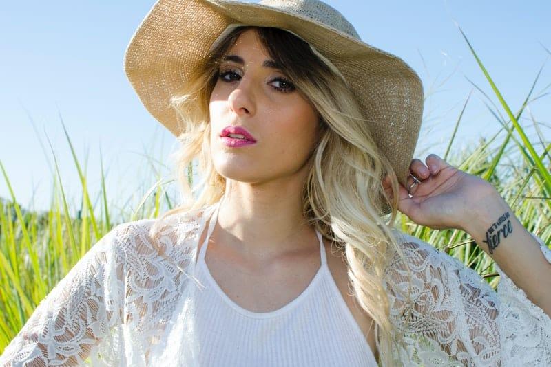 Eine Blondine mit einem Hut auf dem Kopf sitzt auf einem Grasfeld
