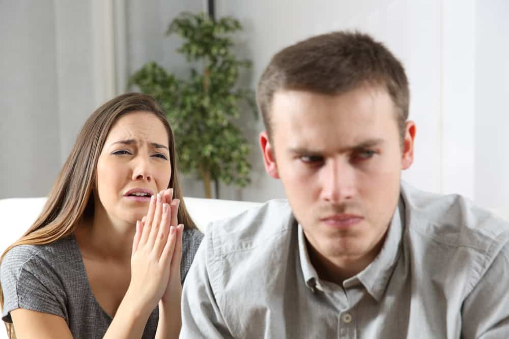 Eine Frau bittet einen Mann in einem Hemd, ihr zu vergeben