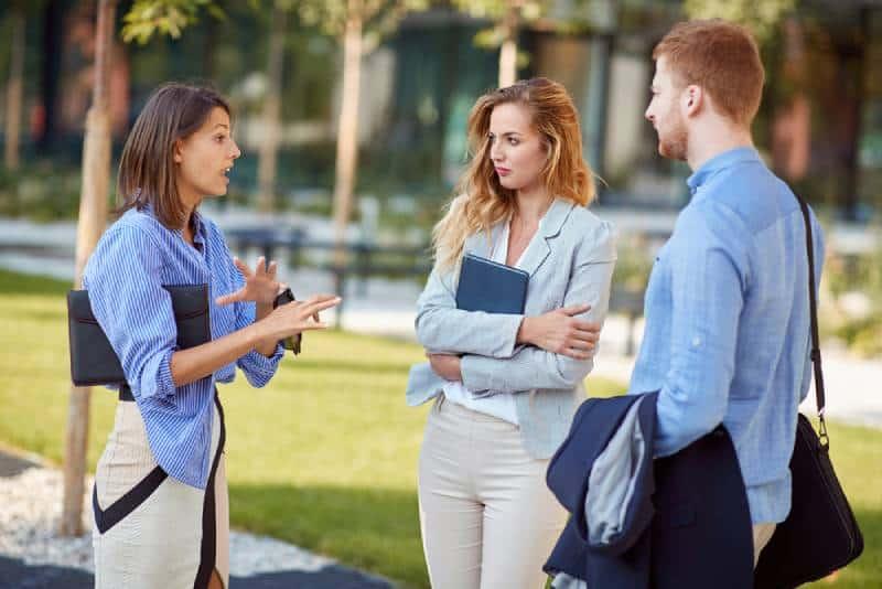 Eine Frau erklärt und gestikuliert ihren Kollegen, Geschäftspartnern
