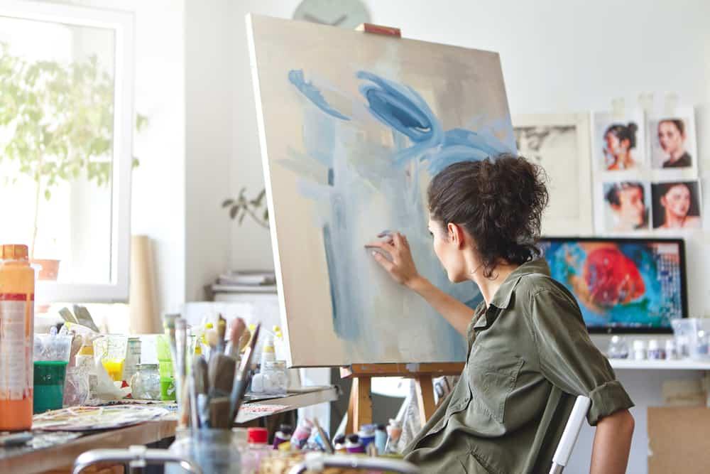 Eine Frau malt eine Hand auf die Leinwand