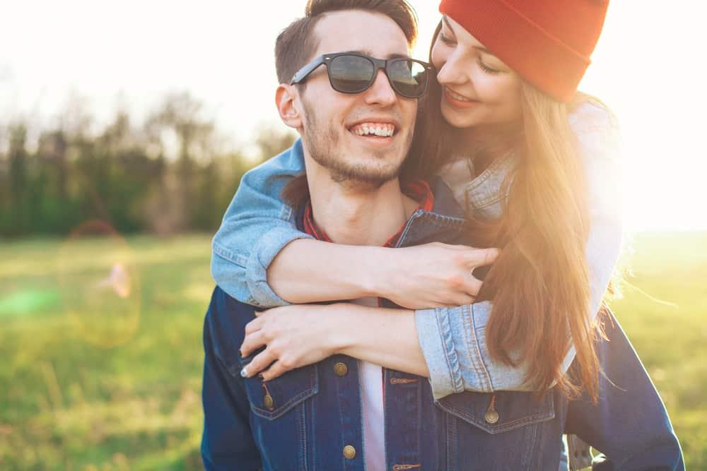 Eine Frau mit roter Mütze umarmt einen lächelnden Mann von hinten