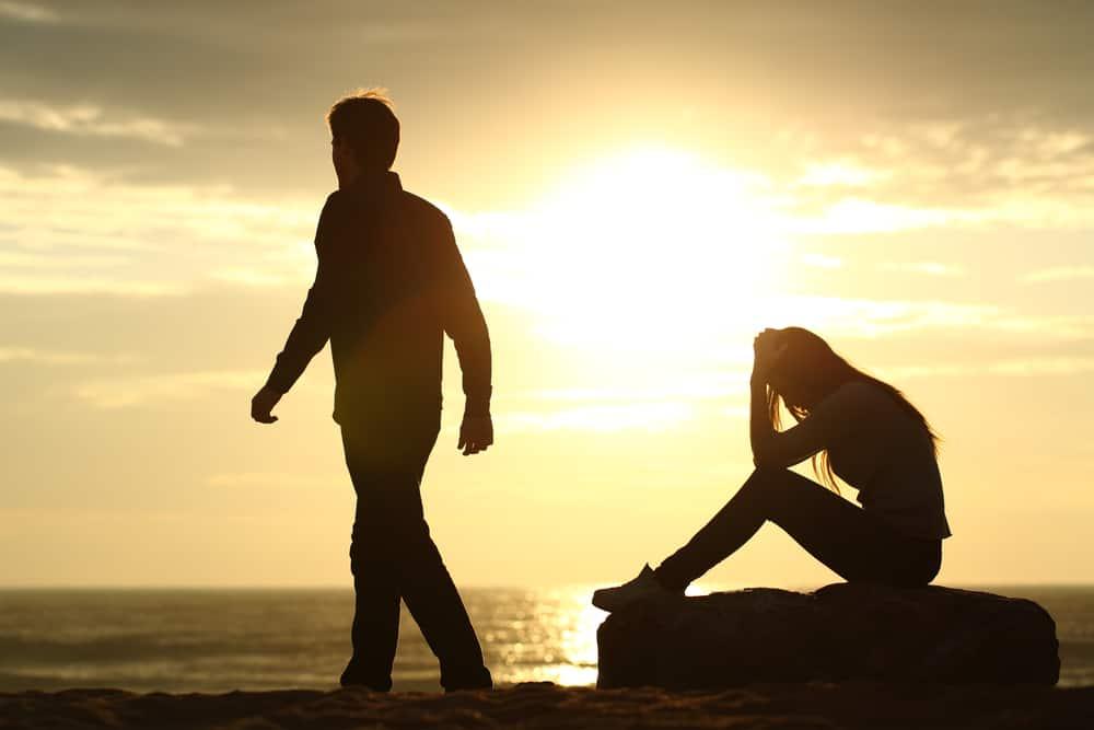 Eine Frau sitzt mit gesenktem Kopf auf einem Stein, als ihr Mann sie verlässt