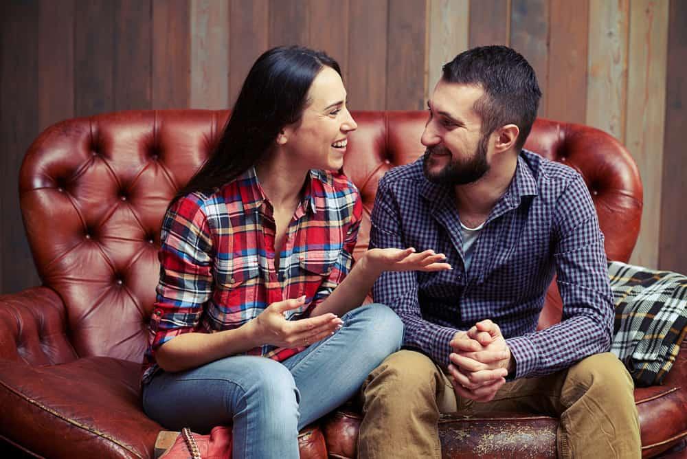 Eine Frau und ein Mann sitzen auf einem Ledersofa und unterhalten sich