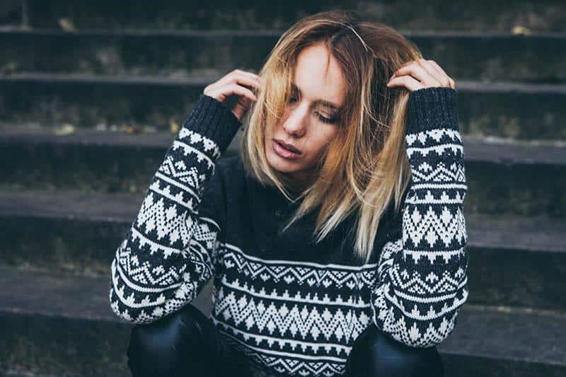 Eine enttäuschte Frau in einem Pullover sitzt auf der Treppe