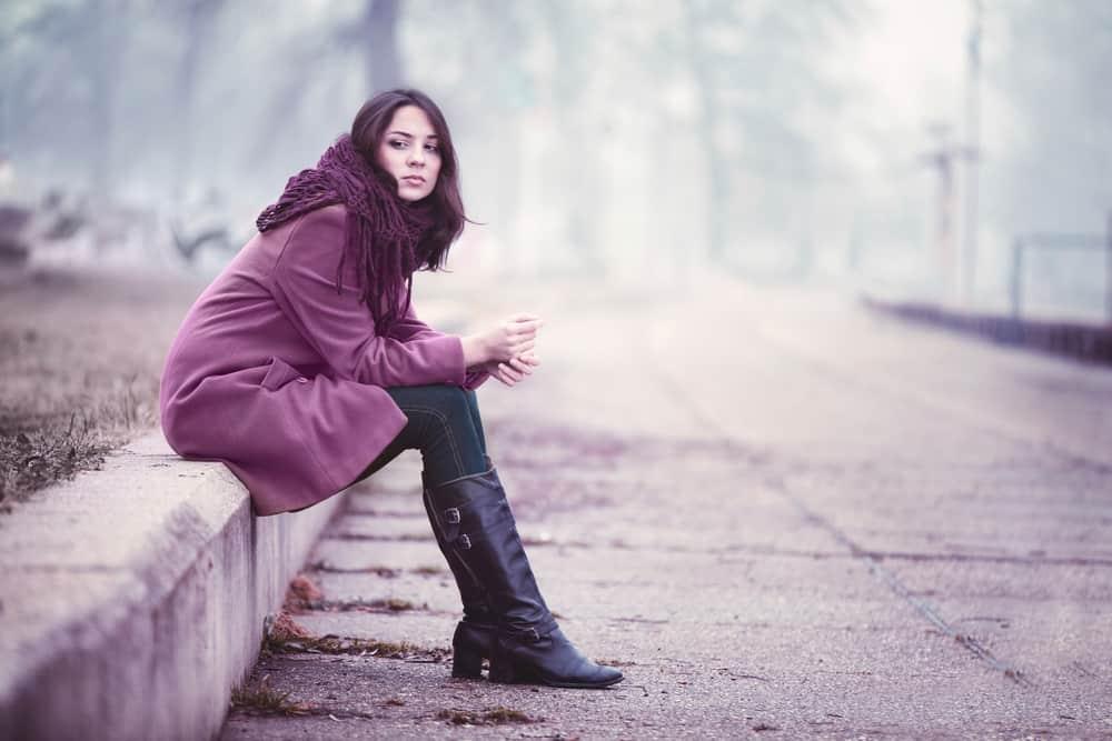 Eine enttäuschte junge Frau sitzt mit gekreuzten Beinen auf einer Betonwand