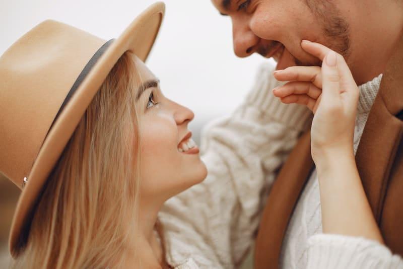 Eine lächelnde Blondine mit Hut sieht ihrem Mann in die Augen und streichelt sein Gesicht