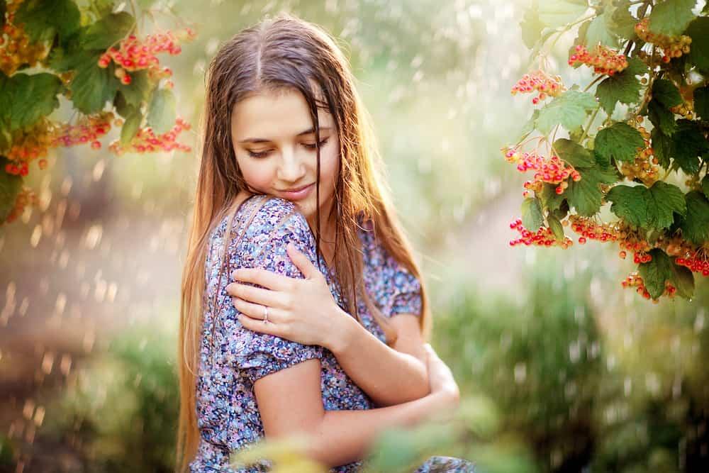 Eine schöne Brünette in einem bunten Kleid umarmt sich