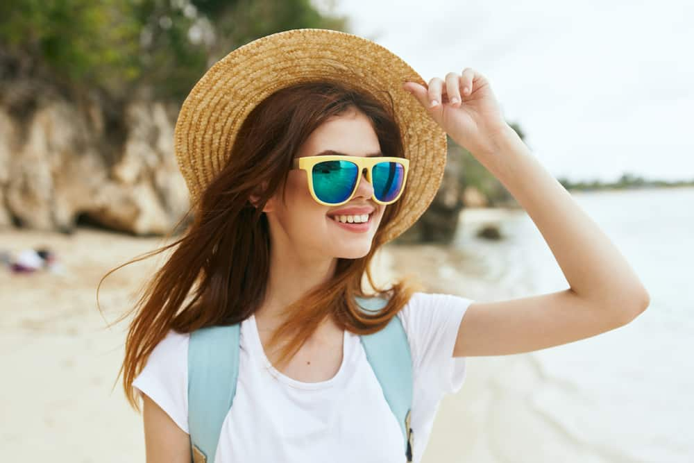 Eine schöne junge Frau mit Sonnenblumen geht am Strand spazieren