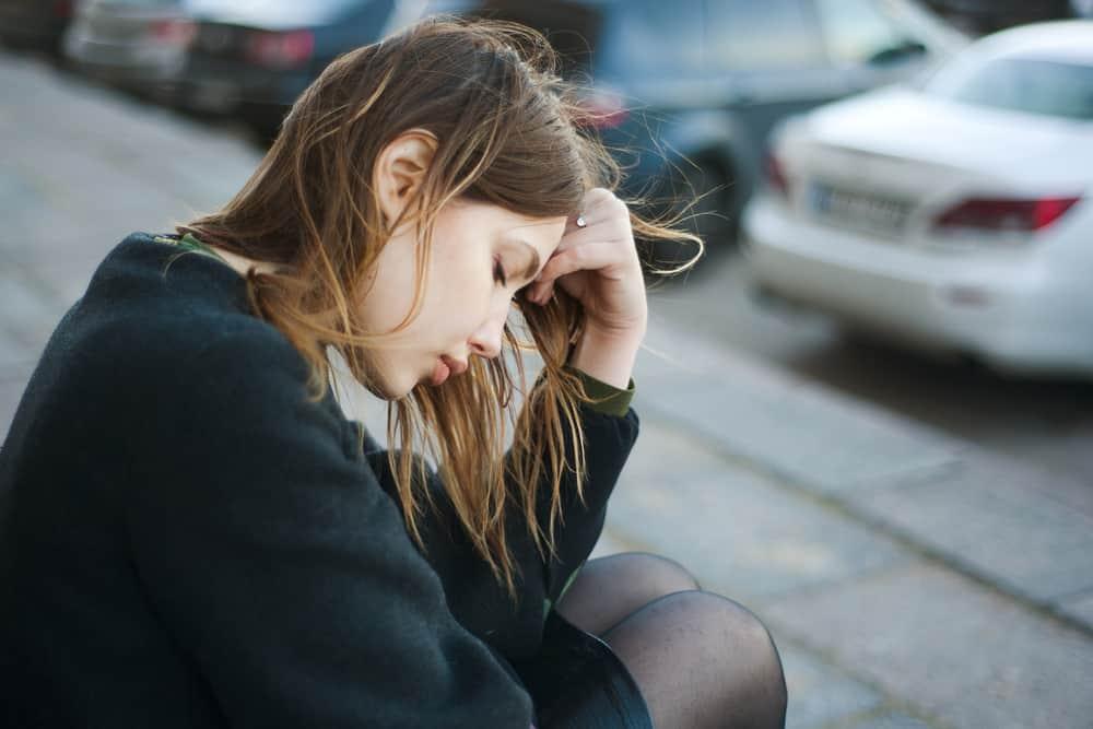 Eine traurige Brünette sitzt mit gesenktem Kopf auf der Treppe
