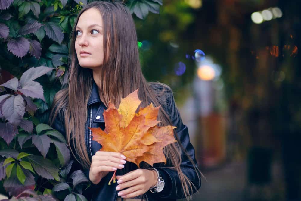 Eine traurige Brünette steht draußen mit Blättern in der Hand