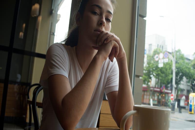 Eine traurige Frau sitzt in einem Café und denkt nach