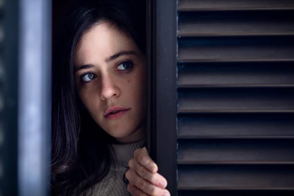 Eine verängstigte Frau späht aus dem Fenster